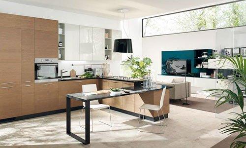 Un monolocale con la cucina di color legno chiaro con tavolo angolare di color nero a distanza mobile tv di color turchese