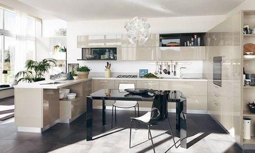 Una cucina di color crema lucido con penisola e un tavolo di color nero al centro