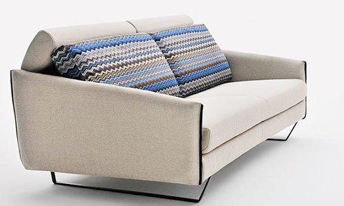 Un divano a due posti con cuscini ricoperti in stoffa multicolore e la schienale pieghevole