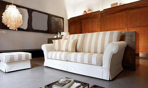 Un salotto con divano a tre posti di color beige con cuscini a righi di color crema e marrone chiaro, un mobile in legno dietro e un lampadario bianco a sospensione