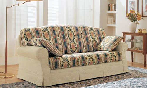 Un divano a tre posti ricoperto in stoffa di color crema e fiori a multicolore, una lampada da terra sulla sinistra e un mobile in legno con vaso di fiori sulla sinistra