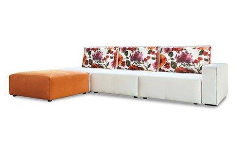 Un divano angolare di pelle di color bianco e cuscini ricoperti in stoffa con fiori di color rosa e arancione e un pouf di color arancione nell'angolo