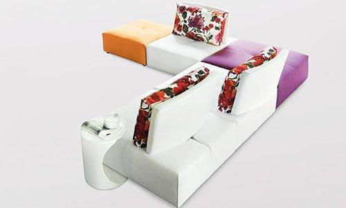 Un divano angolare in pelle dal dietro di color bianco, arancione e viola e disegni di fiori  su uno sfondo bianco