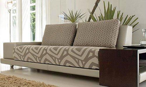 Un divano a tre posti di color crema con dei disegni geometrici,  una lampada da terra sulla sinistra, delle piante dietro a davanti un tappeto