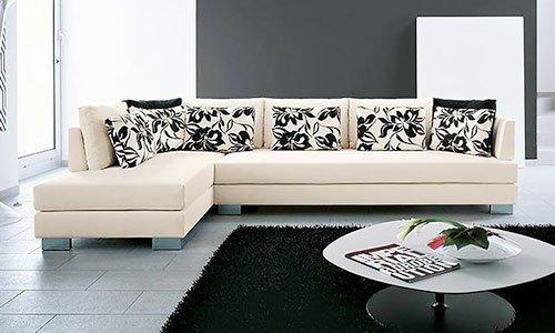 Un divano angolare di color crema con dei cuscini di color bianco e nero con disegni di fiori, un tavolino rotondo davanti  e un tappeto di color nero
