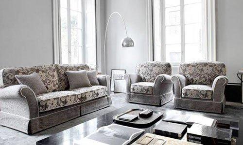 Una sala con divano a tre posti e due poltrone ricoperti con una stoffa di color marrone e disegni di fiori, una lampada da terra in acciaio  e un tavolino in legno al centro con dei libri