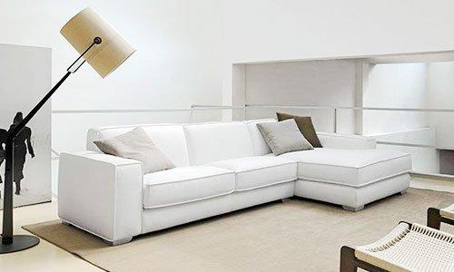 Un divano angolare di color bianco, due sedie davanti e una lampada da terra di color nero