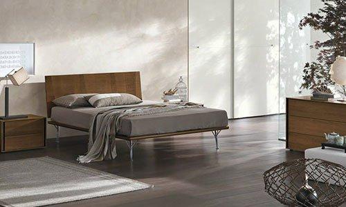 una camera da letto moderna con testata in legno, letto sfatto con coprimaterasso grigio sulla sinistra un comodino con una lampada