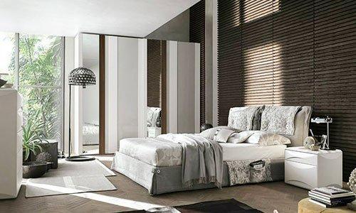 una camera da letto moderna con testiera bianca, letto sfatto con un coprimaterasso bianco