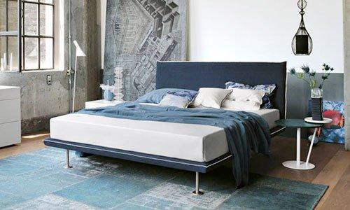 una camera da letto con letto color blu e bianco sfatto, sulla destra un tavolino verde con sopra un vaso di fiori e al centro della stanza un tappeto color verde smeraldo