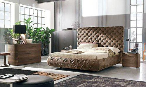 camera da letto con testata del letto e letto imbottiti di color beige, sulla destra un comodino di legno con una lampada e sulla sinistra un como in legno con sopra una tv