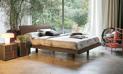 una camera con sulla sinistra due piccoli comodini in legno con sopra una lampada, un letto in legno con coprimaterasso beige e cuscini marroni, una sedia rossa, una pianta e una finestra da cui si riesce a vedere il giardino con degli alberi
