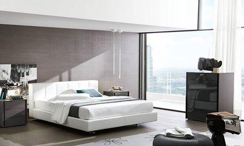 Una camera con un letto di color bianco, comodini e un como' di color grigio scuro e un pouf davanti