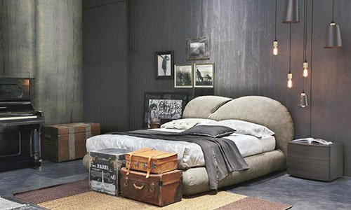 Un letto con testata imbottito di color marrone chiaro, lampadine a sospensione, e vaglie antiche davanti il letto