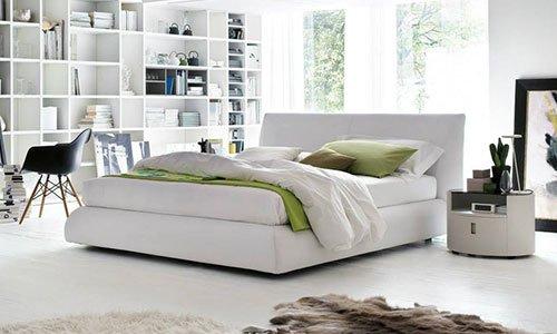 Una camera con letto di color bianco in centro, sulla destra una libreria, una sedia davanti e sulla destra un comodino rotondo