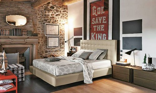 Una camera con un camino sulla sinistra, un letto  in pelle di color crema, due comodini in legno scuro sulla sinistra e cornici appese sul muro e un tavolino davanti di color arancione