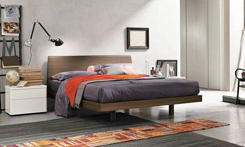 Una camera con letto di color marrone, comodino di color bianco e davanti un passatoia multicolore