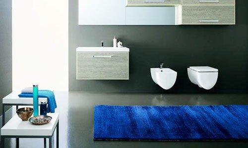 Un bagno con muri di color grigio scuro, bidet e wc al muro, dei cassetti in legno e un tappeto di color blu davanti