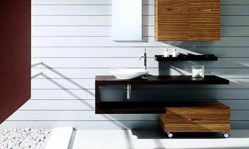 Un bagno con uno specchio lungo , mobile con ante in legno scuro e un lavandino bianco
