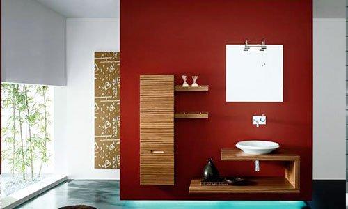 Un bagno con un muro di color rosso, mensole in legno con oggetti , un lavandino bianco e uno specchio al muro
