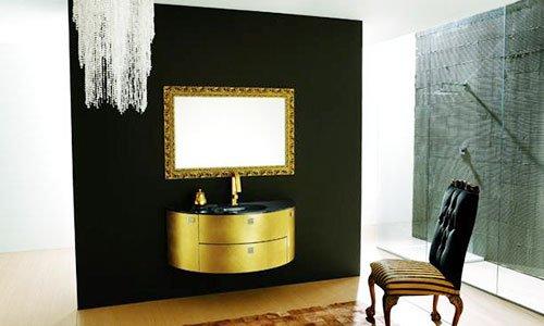 Un bagno con muri di color nero, un lavandino nero, mobile con cassetti di color dorato, uno specchio al muro con cornice dorata e davanti una poltrona