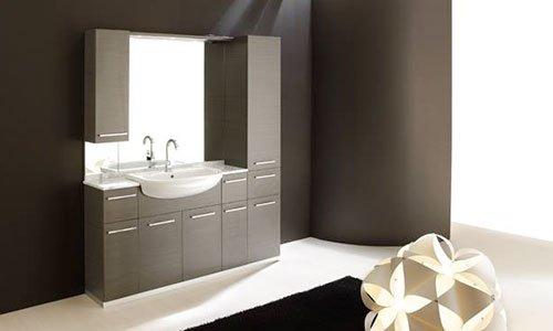 Una bagno con mobile di color grigio scuro con delle ante, specchio e lavabo