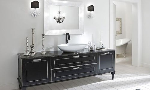 Un mobile nero con un portacandele in acciaio, dei cassetti e un lavabo e vista di un'altra stanza con la vasca