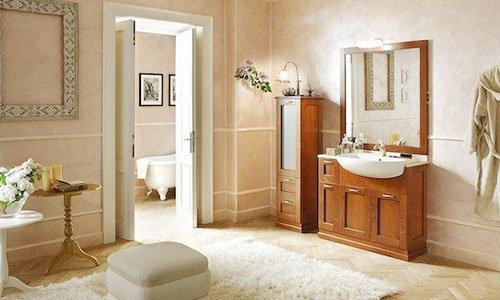 Un bagno con un mobile in legno con lavabo e davanti un tappeto bianco, un pouf in mezzo e vista di un'altra stanza con la vasca