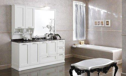 Un bagno con la vasca sulla destra e sulla sinistra un mobile bianco con un lavabo, delle ante e davanti un sgabello imbottito con le gambe in legno