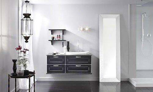 Un bagno con uno specchio con una cornice bianca appoggiata al muro,un box doccia  e un lavabo con un mobile nero sotto