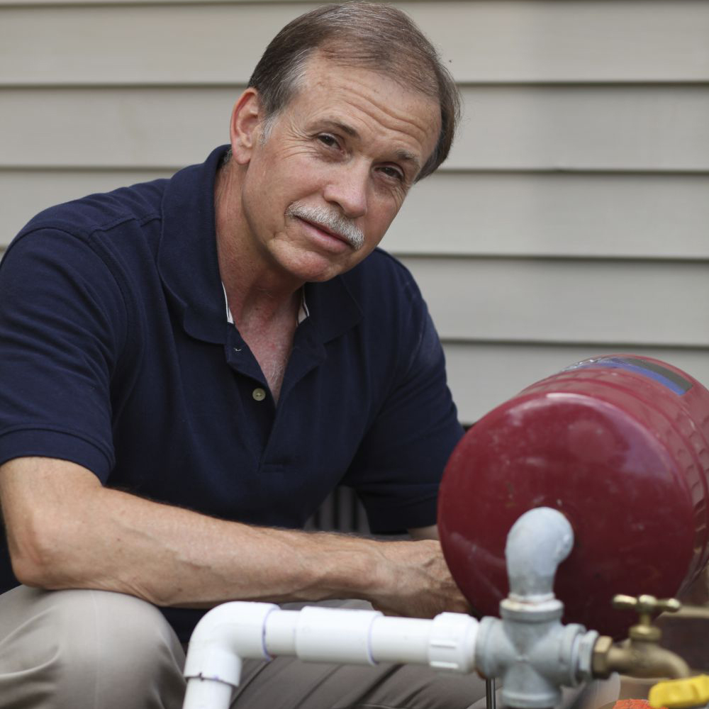 A mechanic of Washington Pump and Drilling sitting next to a red part of a pump system