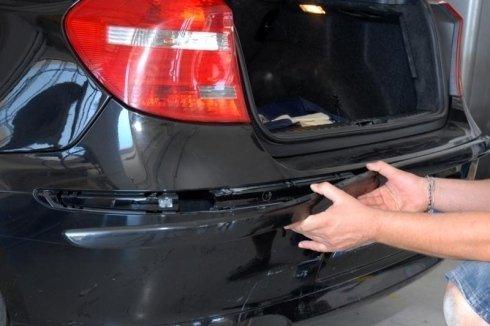 Le mani di un carrozziere stanno montando un paraurti posteriore