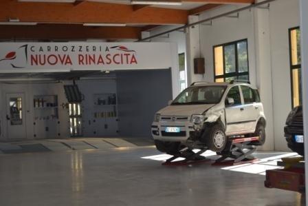 Auto su una pedana di sollevamento all'interno della Carrozzeria Nuova Rinascita di Campofilone