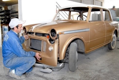 carrozziere in tuta monta il paraurti di un'auto d'epoca