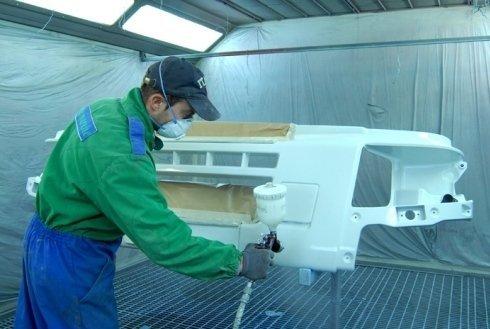 carrozziere con mascherina che dipinge il davanti di un veicolo