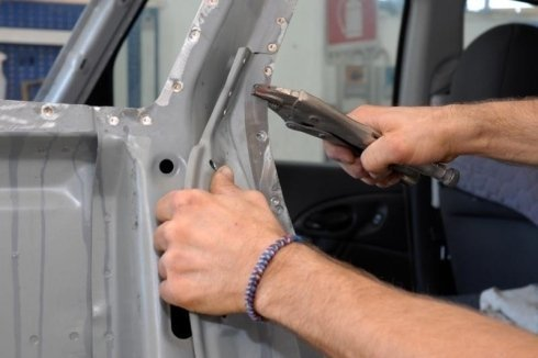 le mani di un carrozziere impegnate nel raddrizzamento di un telaio