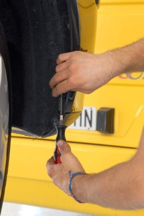 le mani di un carrozziere impegnate nel montaggio