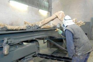 carrozziere impegnato nella verniciatura di un componente
