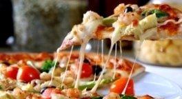 Primo piano di una fetta di pizza con verdure e mozzarella