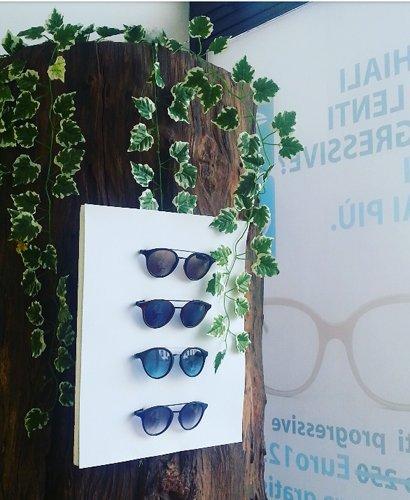 quattro paia di occhiali da sole attaccati a un pannello bianco