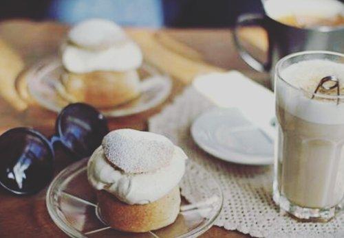 occhiali da sole sopra un tavolo con due muffin e un latte macchiato