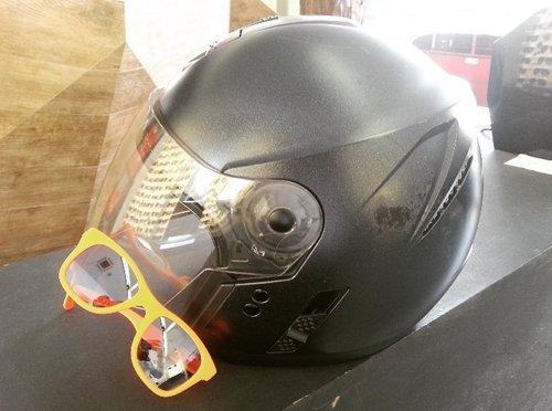 casco per la motocicletta e un paio di occhiali da sole con montatura gialla