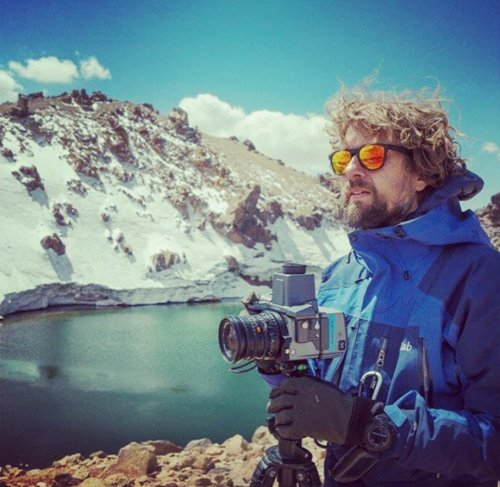 uomo con macchina fotografica vicino a delle montagne innevate