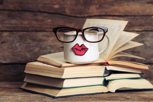 occhiali da vista con montatura tonda sopra una pila di libri e vicino a una tazza da caffe