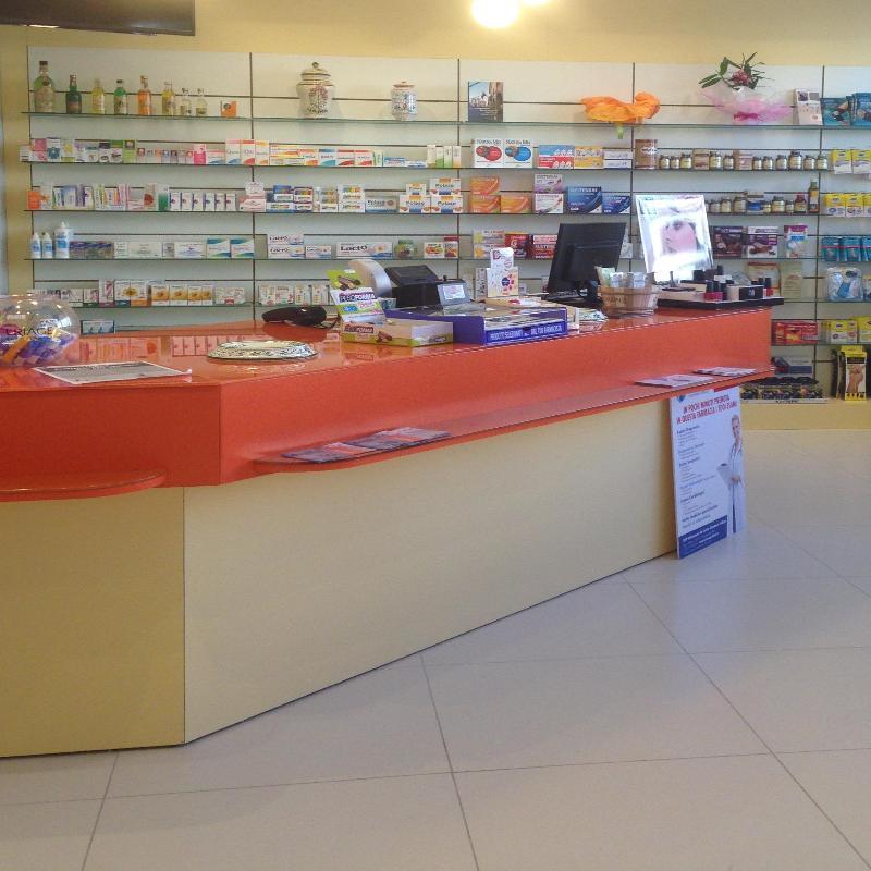 Il bancone di una farmacia e delle mensole con dei prodotti esposti