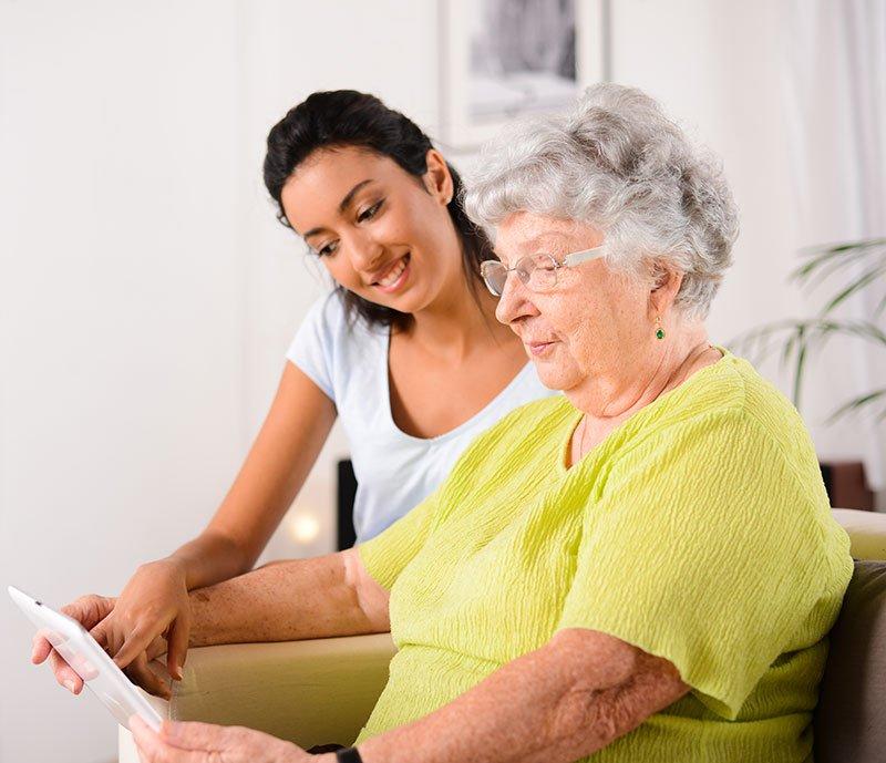 giovane donna che assiste una donna anziana a leggere