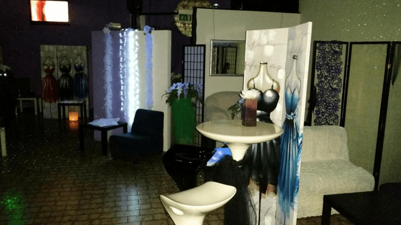 Un tavolino bianco con uno sgabello e un pannello divisore con degli abiti disegnati