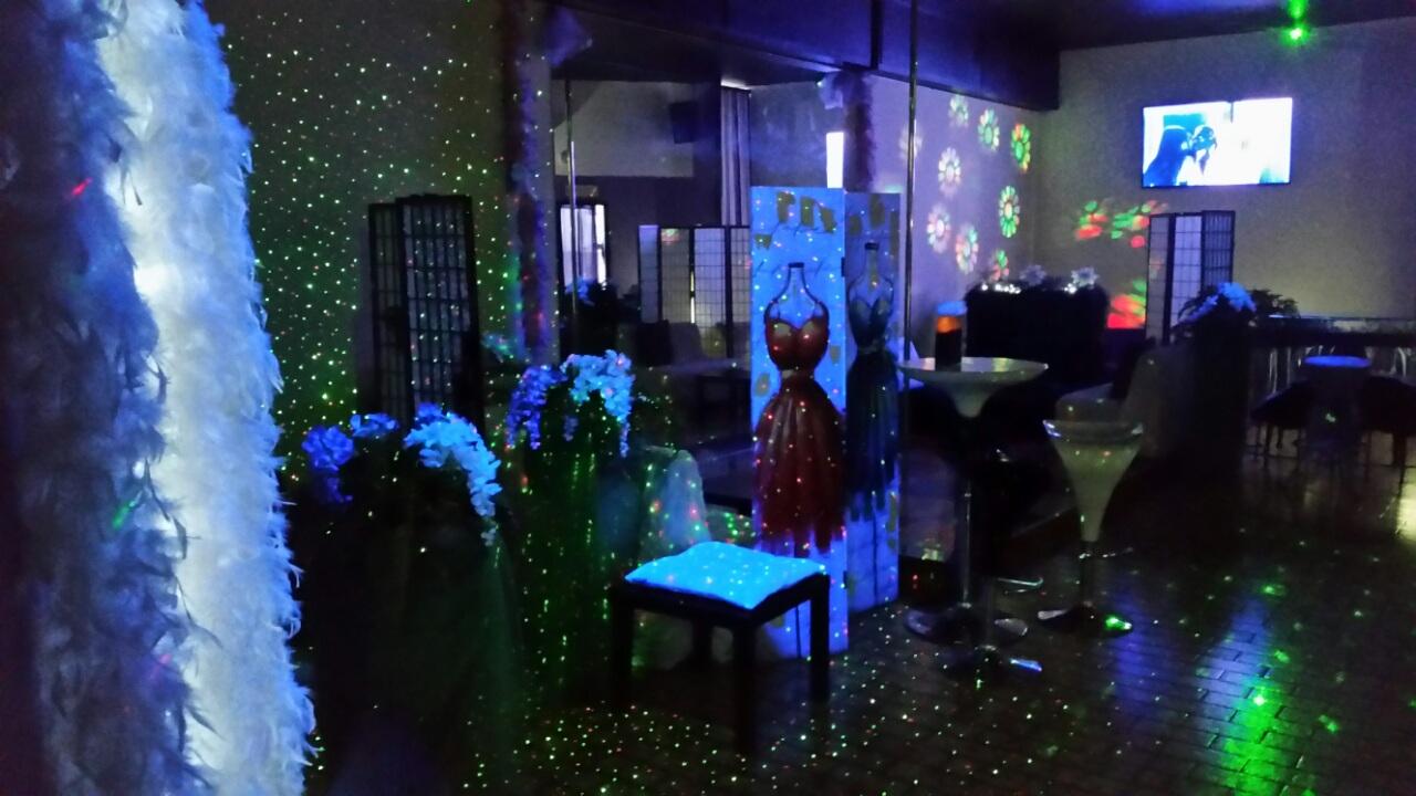 Decorazioni con piume bianche, sgabelli e tavoli all'interno di un night club