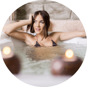 A woman enjoying a hot tub with candles