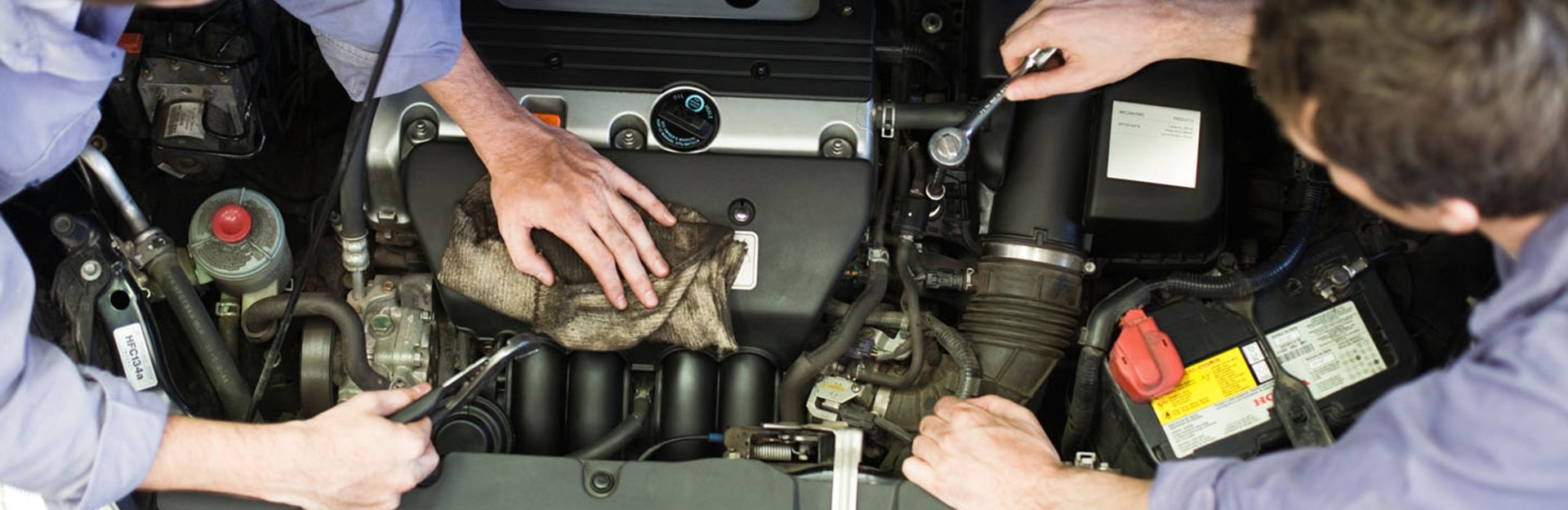 Two mechanics working on a car engine